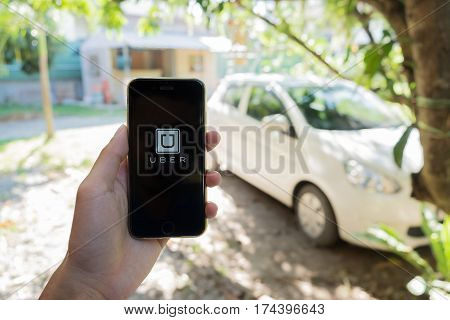 HIANG MAI THAILAND - JAN 15 2017 : A man hand holding Uber app showing on iPhone 6S Uber is smartphone app-based transportation network.