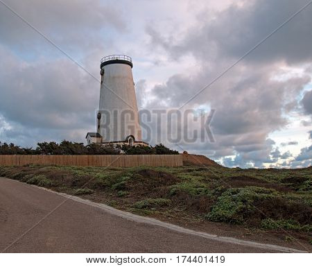 Lighthouse at Piedras Blancas point under overcast sunset clouds on the Central California Coast north of San Simeon California USA