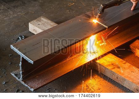 Worker cutting steel H-beam using metal torch in manufacturing factory.