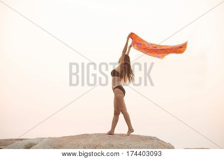 Positive female holding fabric up and expressing gladness while standing stone on isolated.