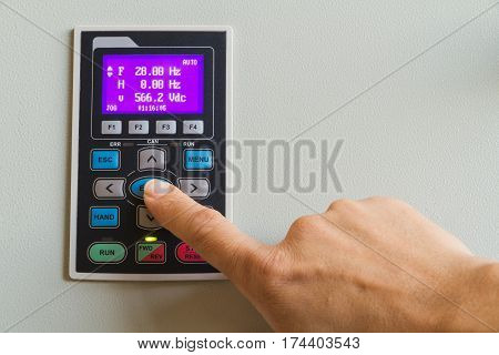 Forefinger touch on enter switch on control panel for machine control.