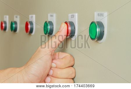 Thumb touch on red stop switch on control panel for machine control.