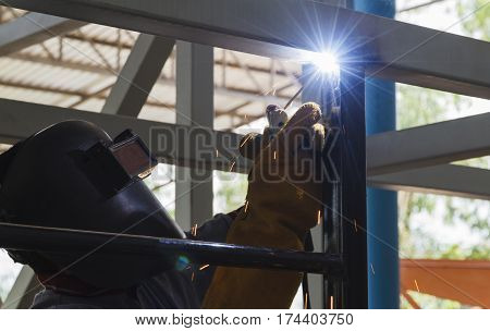 Welder in position over head action were welding steel structural by arc welding - Shield metal arc, At steel structure manufacturing industry.