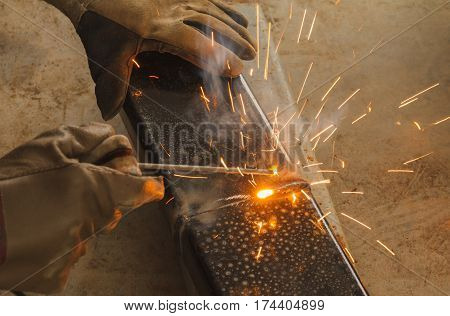 Welder worker using shield metal arc welding joint steel in manufacturing work shop.