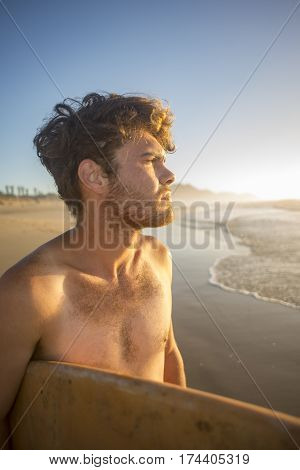 Portrait Of A Surfer With Board Under Arm By The Ocean