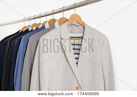 Row of men's suits hanging-white background