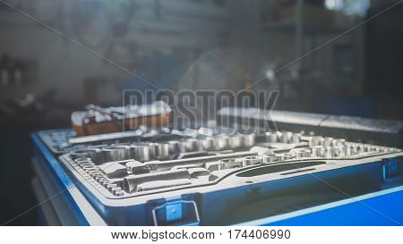 A set of tools for repair - screwdriver, voltmeter, wrenches - car service at sunny day, close up