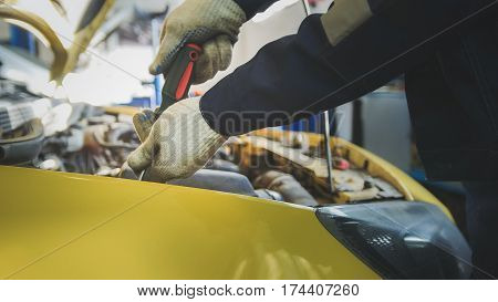 Mechanic unscrews detail of car in hood - automobile service repairing, close up, horizontal