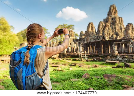 Young Female Tourist Taking Picture Of Bayon Temple, Angkor
