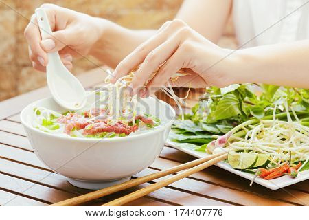 Young Woman Sprinkles Sprouts To The Pho Bo In Vietnamese Cafe