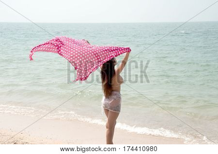 Positive pretty female holding fabric up and expressing gladness on the beach.