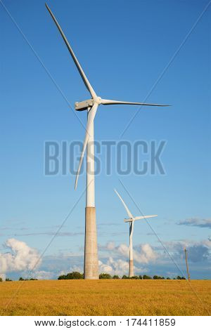 Two wind electric generators in the field in the summer evening. Estonia