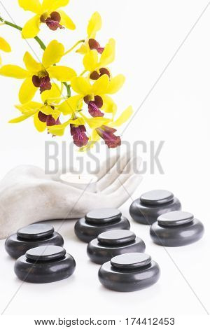 Spa with hot stones, tea light and orchids close up
