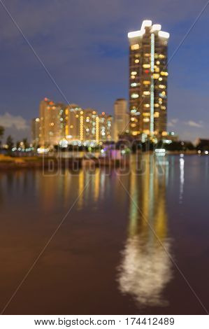 Defocused city building river front with reflection night view abstract background