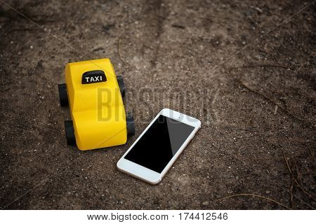 Yellow toy taxi with phone on ground
