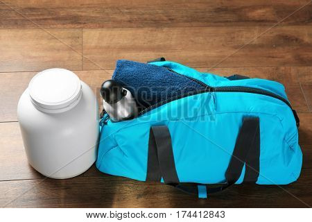 Sport bag with workout objects and supplements jar on the floor