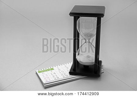 Hourglass with calender on light background