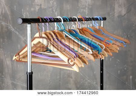 Clothes rail with wooden and colorful plastic hangers on grey background