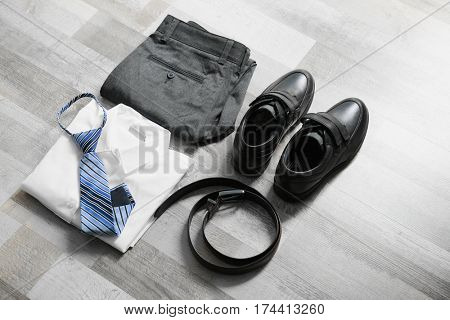Clothes of schoolboy on wooden floor, flat lay