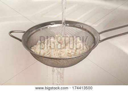 Woman rinsing rice in sifter under running water