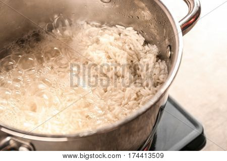 Cooking rice in metal pan on hotplate in kitchen