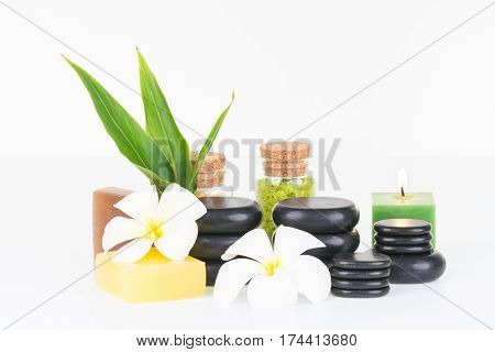 Spa therapy with hot stones, bath salt and soaps on white background