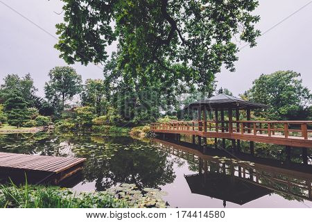 Japanese garden in Wroclaw, Lower Silesia, Poland. Natural park view with little japan pagoda, wooden bridge and small pond.