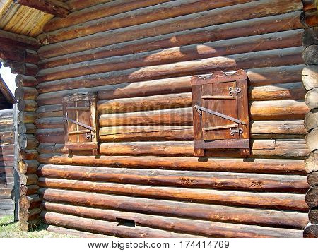 Facade of the barn, fragment. The windows are closed. Closeup. Log hut in Siberian village. Lake Baikal, Russia