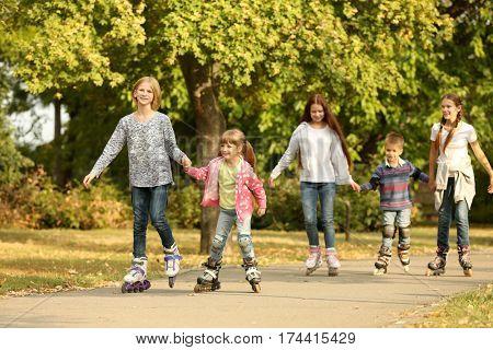 Cheerful children on roller skates in park