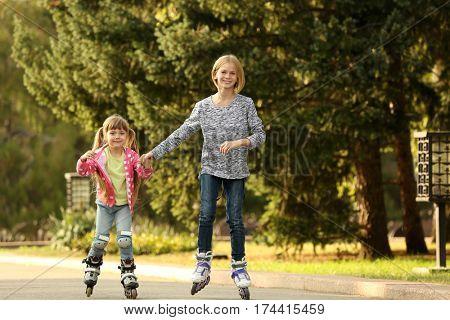 Cute girls on roller skates in park