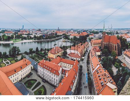 Panoramic aerial view of Wroclaw Old town and Cathedral island roofs with the Holy Cross church by cloudy day. Wroclaw skyline and Tumski ostrow view from above St. John the Baptist cathedral.