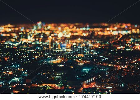True tilt shift shooting of residential district and industrial zone in night metropolis from high point: multiple residential houses teal and orange lights from windows strong bokeh in foreground