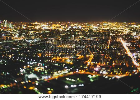 True tilt shift shooting of residential district in night metropolis from very high point: multiple residential houses and warm lights from windows strong bokeh in background and foreground