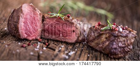 Grilled beef steak with rosemary salt and pepper on old cutting board. Beef tenderloin steak.