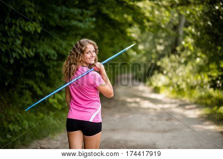 Athletic young woman carrying a javelin over her shoulder as she walks down a rural road turning to smile at the camera