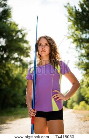 Portrait of young athlete, woman holding javelin - outdoor on sunny day