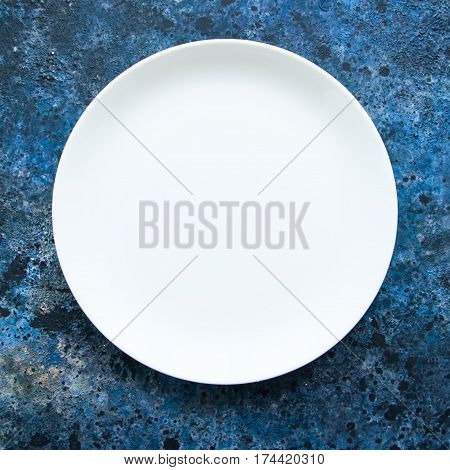 Round empty white plate on a blue textured background. Top view. Copy space.