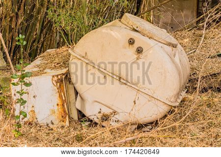 Old refrigerator and septic tank on a ground covered with brown grass and a background of green bamboo in a wooded area in South Korea