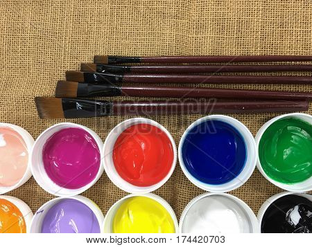 Collage of variety of colorful acrylic paints and art brushes on sacking textile background for the workplace of the artist.