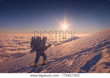 A climber with backpack climbs up a snowy slope. Sunset sky on a horison.