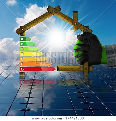 Hand with work glove holding a wooden ruler in the shape of house with energy efficiency rating above the solar panels. Concept of ecological house project