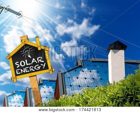 Roofs of houses with solar panels power line and a sign with text Solar Energy On a blue sky with clouds and sun rays