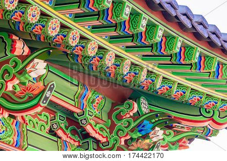 Eve of a Buddhist temple building with vibrant green red blue and white colors representing the Lotus flower which is sacred to the Buddhist religion