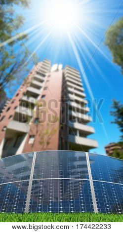 Group of solar panels in front of an apartment building with clear blue sky and sun rays