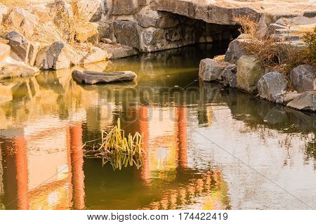 Closeup of a small pond at a Buddhist temple with green plants growing in the middle of the pond and beautiful reflections of the plants the stones around the pond and of a temple building next to the pond