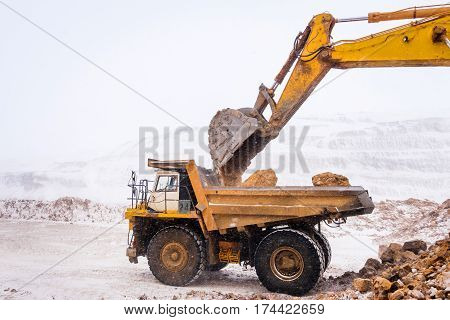 Truck loading with ore. Excavation. Gold mining