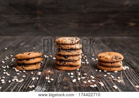 Three stacks of crisp chocolate chip cookies on a dark wooden table.