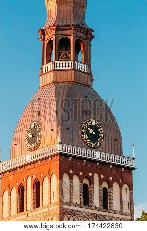 Close Up Of Clock On Tower Of Riga Dome Cathedral In Riga, Latvia. Sunny Blue Sky Background. Bellfry Bell Tower In Golden Hour At Sunset Or Sunrise Time