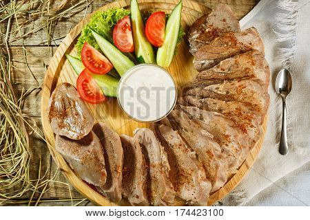 Raw meat with herbs, seasonings, tomato cherry, cucumbers and white souce cream on wooden round table. Row beef steak grill pan stove with spices.