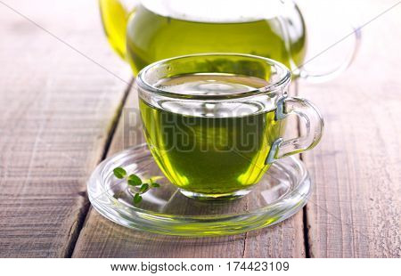 Green herb tea in glass cup and teapot